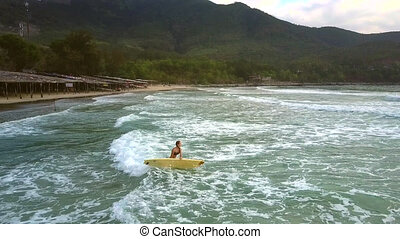 girl carries surfboard to foamy ocean waves - strong girl...