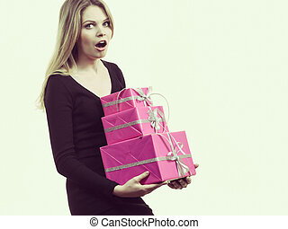 Girl carrying many pink gift boxes