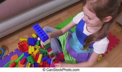 Girl casts a tower of play bricks