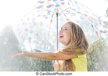 Girl catching raindrops - Girl with umbrella catching...