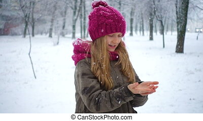 girl catching snowflakes at the winter park