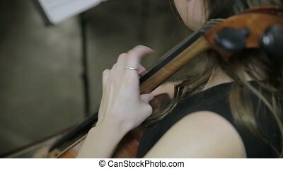 Girl cellist playing cello Close up