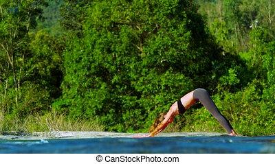 girl changes cobra pose to downward-facing dog on bank