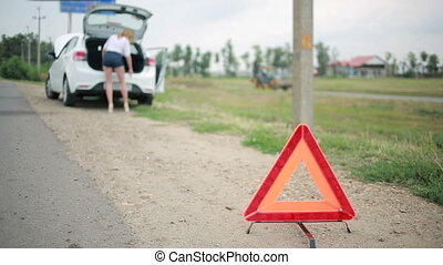 Girl changing a punctured tire at the car. repair of cars on the road. accident