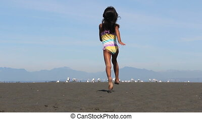 Girl Chasing Down Birds At Beach