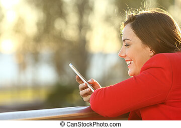 Girl checking smart phone outdoors in winter