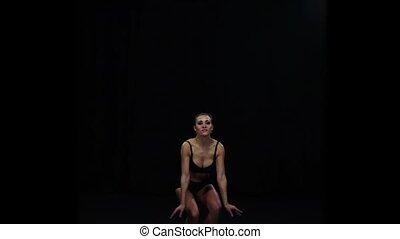Girl cheerleader jumps bending your knees. Black background....