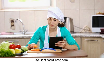 girl chef browses her tablet