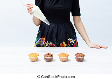 Girl chef with piping bag with the cream, cupcakes on white wooden table