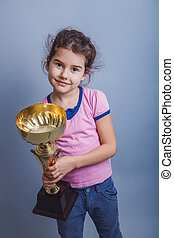 girl child 6 years of European appearance holds a cup in his...