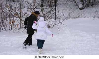 Girl child and teenager boy playing snowballs. Brother and sister having fun in winter park. They run around and laugh. Frosty winter cloudy day