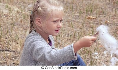 Girl child blowing fluff of bulrush - Girl child in the...