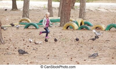 Girl child chasing pigeons - Girl child runs through the...