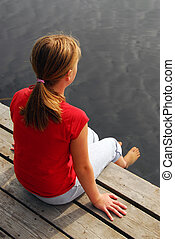 Girl child dock - Young girl dipping feet in the lake from a...