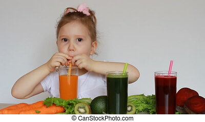 Girl child drinks vegetable smoothies - Carrot, beet and...