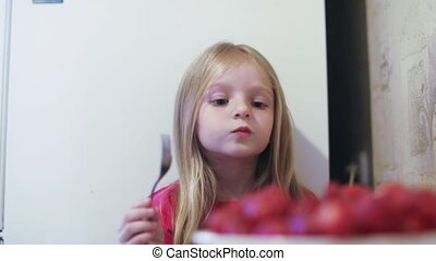Girl child eating strawberries - At the table, the little...