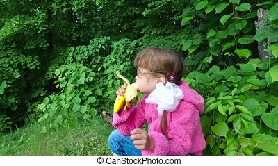 Girl child eats banana in a summer forest. The girl has a good appetite in the fresh air. Fruits are very tasty. Summer evening in the forest.
