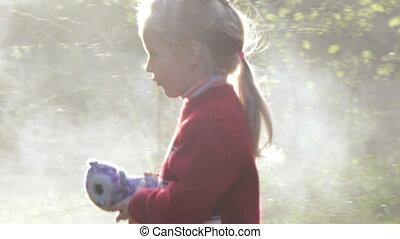 Girl in refugee dense smoke extinguish fire in backlit sun
