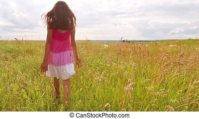 girl child goes on nature by field grass summer sunlight...