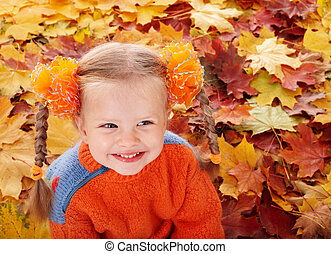 Girl child in autumn orange leaves.