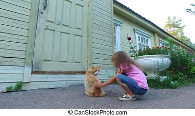 Girl child in glasses stroking the old red cat. Little girl smiling and pretty cat purrs.