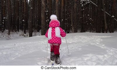 Girl child is learning to ski. She slowly slides on skis in soft fresh snow. Beautiful day in the winter forest