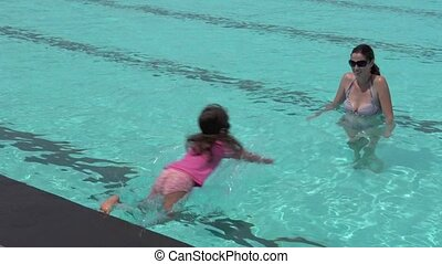 girl child jumps into swimming pool