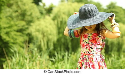 Summer. Little girl child kid putting on the black straw hat on the meadow or in the park outdoor.