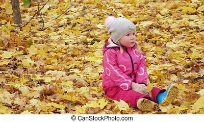 Girl child lies on leaves - In autumn park girl child lies...