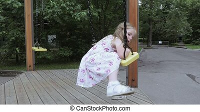 Girl child on a chain swing