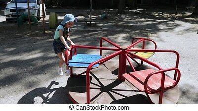 Girl child on carousel - On the playground in the yard of...