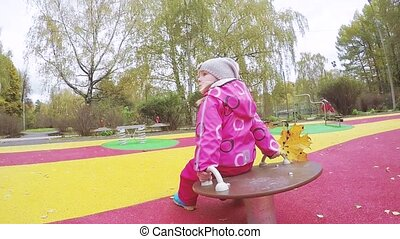 Girl child on rotating swing