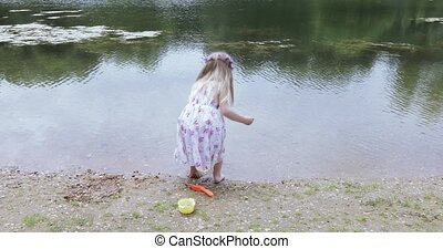 Girl child on the shore of a pond