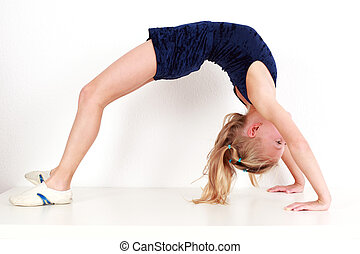 Girl child performing backward bend gymnastics on white background
