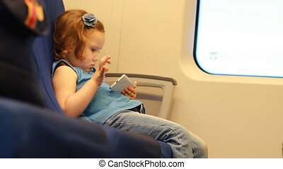 Girl child play with smartphone in train. Baby playing game on the mobile phone in the express train.The concept of travel, trip, road