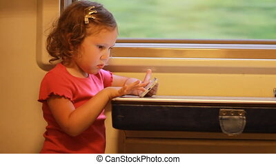 Girl child play with smartphone in train. Baby playing game on the mobile phone in the road.