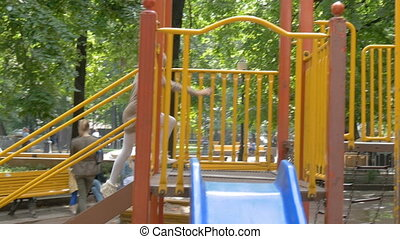 Girl child playing on the playground. Sunny summer day.