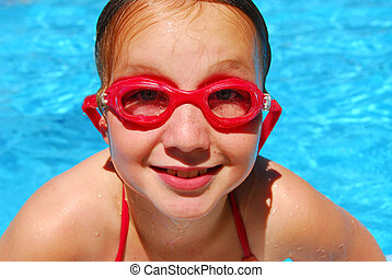 Girl child pool - Portrait of a smiling girl in red goggles