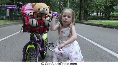 Girl child repairs bicycle - In the park the little girl is...