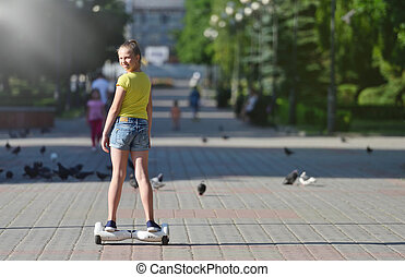 Girl child riding a hoverboard on a sunny day and turning back looking at the camera