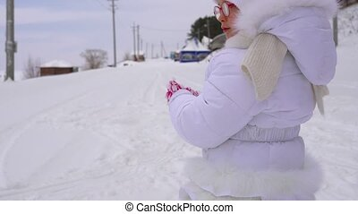 Girl child runs on snow-covered road. Active holidays for children in winter park. A cloudy winter day