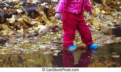 Girl child runs through puddles