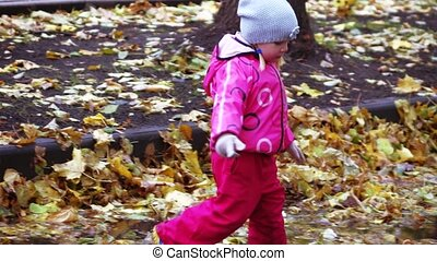Girl child runs through puddles - In autumn park Girl child...