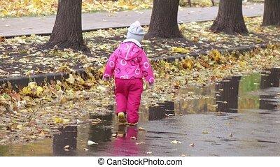 Girl child runs through puddles - In autumn park Girl child...
