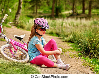 Girl child sitting near bicycle.