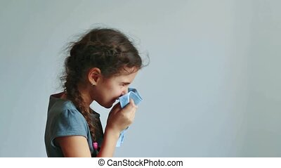 girl child sneezes into handkerchief on a gray background....