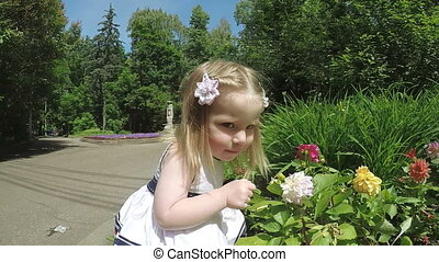 Girl child sniffing flowers