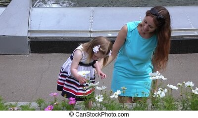 Mom with a girl in the park sniffing flowers