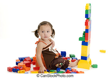 Adorable two year old Japanese American girl playing with colorful plastic building blocks.