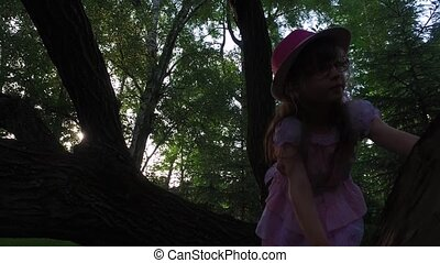Girl child tries to climb a tree. But she can not. She is still small. Old overgrown park. Summer sunny evening.